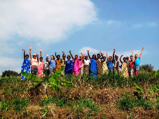 DANCE TO THRIVE:  Through her World Dancers for Humanity, Janet Reineck (center, in pink) raised funds to help women of the Twirererabana Cooperative purchase this farmland in Rwanda.