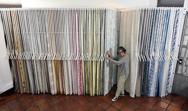 <b>LINENS AND THINGS:</b> Susan Owens hangs with Sally McQuillan's internationally renowned fabrics in the lower State Street shop.