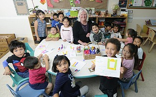 Lorraine Neenan surrounded by the children of Community Action Commission's  Los Ninos Center day care.