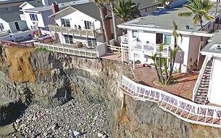 The owners of two apartment buildings on Del Playa Drive in Isla Vista — 6663, shown with a new chainlink fence blocking access to the balcony, and 6653, next door to the right — must come up with engineering solutions following Sunday's cliff collapse, county officials say. James Gelb, owner of 6653 Del Playa, says he plans to demolish the two apartments on the west end of his building, shown here, and two on the east end. A portion of the balcony from 6653 Del Playa is lying below the rock slide.