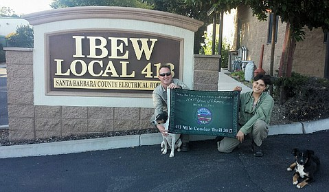Monica and Justin Kennedy pose with their pups in front of their labor union's Santa Barbara headquarters