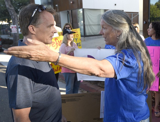 John Lawrence (left) engages with Planned Parenthood protesters, including Teresa Marsano (right)