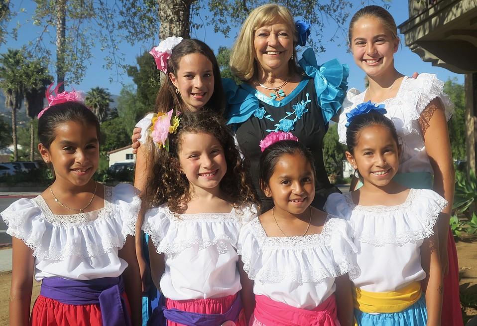 Executive Director Lynn Brittner flanked by Fiesta flower girls.