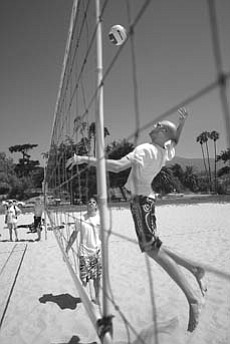 Todd Rogers and Phil Dalhausser (going for the spike) practice at East Beach.