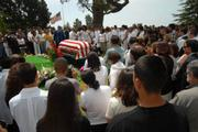 With the American flag at half-staff in the background, mourners pay their last respects  to Spc. Jaime Rodriguez Jr. before his burial at Santa Barbara Cemetery.