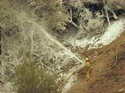 Fire fighter sprays a mixture of soap and water on one of the hand lines that they will need to hold.