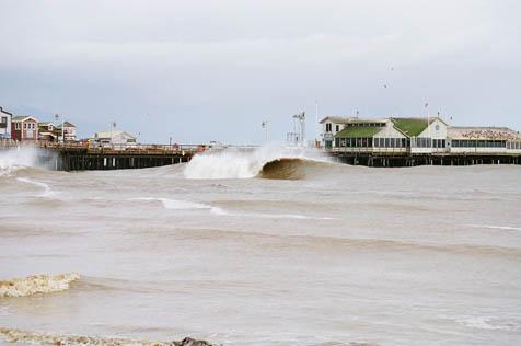 This photo was taken from the beach west of Stearns Wharf on January 30, 1998. The wind was blowing hard out of the south, causing a southeast wind swell to couple with the large northwest swell. Late in the morning, the wind switched 180 degrees to the northwest. Knowing there was huge surf and offshore winds at the harbor, I grabbed a camera, covered it to protect it from the light rain, and took the shot. I was planning on surfing that day, but the breakwater was closed and there were trees floating in the brown water. -Mark Morey