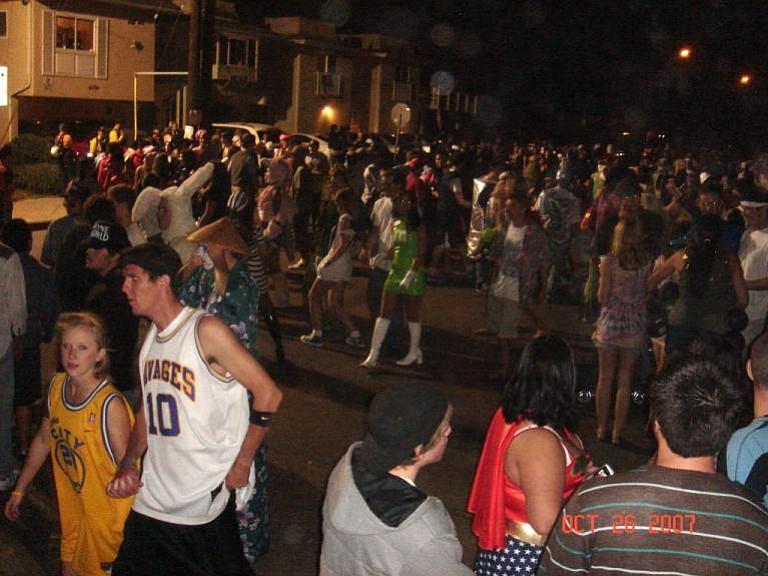 Halloween revelers crowd Del Playa Drive.