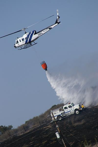 A helicopter drops water on the November 3 brush fire near Highway 246.