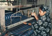 This Bangladeshi woman weaves a bolt of Grameen Check, a cotton fabric native to that country.