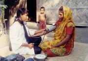 A paramedic from Grameen Kalyan, a spinoff company created by Grameen Bank in 1996 to provide health and welfare services to members and staff of the bank, consults with a villager who might otherwise have little opportunity to receive healthcare.