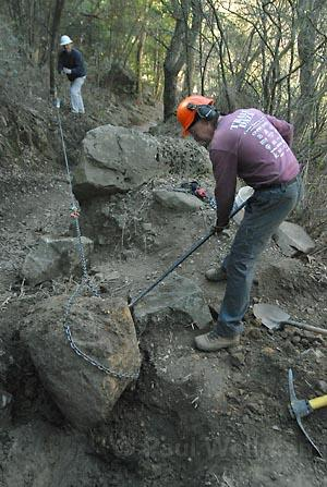 Ray Ford (background) and Paul Herning (with shovel) winched, wiggled, and pried a massive rock on a lower stretch of the Cold Spring trail last week as part of trail rehab efforts.