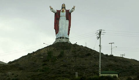 A large, strangely-proportioned statue of Jesus overlooks the Pacific Ocean near Puerto Nuevo.