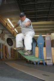 Surrounded by a historical quiver of boards, be they for the surf, concrete, or snow, Chuck Barfoot demonstrates an ollie on one of his first snowboard designs, from the late 1970s, at his factory in Ventura earlier this Winter.
