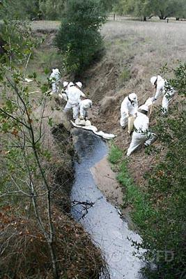 The County Fire HazMat crew works to clean up a Greka oil spill in a creek earlier this year. The energy company has spilled 20 more times since an emergency Supervisor hearing was held about their nasty habits less than two months ago.