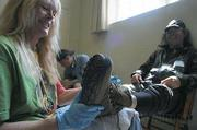 Volunteer Kathrin Pfeiffer (l) fashions Luis Becerril (r) with a new pair of shoes