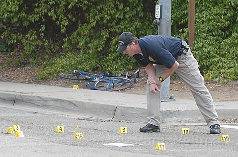 Police investigator Mark Hunt looks over evidence in the intersection of Mission St. and 101 Southbound onramp.