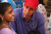 Vitamin Angels' founder Howard Schiffer speaks with a mother at a vitamin distribution in the slums of Pune, where more than half of the city's 2.5 million people live in more than 500 slums.