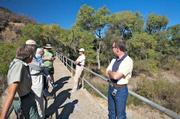 City and Forest Service officials sit against the top railing of Mono Debris Dam discussing different options for controlling the amount of sediment coming into Gibraltar Reservoir. There are few options given the remote location, costs and environmental issues.
