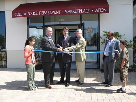 Ellwood School students hold the ribbon as, from left, Goleta Mayor Michael Bennett, Sheriff Bill Brown, and Camino Real Marketplace developer Mark Linehan celebrate the opening of the new Goleta police station while city councilmember Roger Aceves watches.