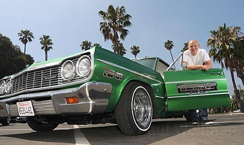 Lowrider Cab owner Benny Bermudez stands by one of his rides.
