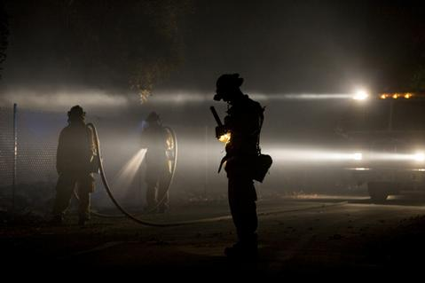 A fire crew works on the steadily burning roadside.