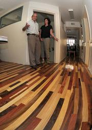 EDC Executive Director David Landecker (left) and Chief Council Linda Krop display the office's new flooring made from local wood