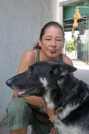 """Rescue dog:  When Christhea Puglia was assaulted in Dwight Murphy Park last week, her dog stopped the attack. Homeless outreach worker Ken Williams said violent attacks against the homeless are increasing. """"These are cowards hunting these people,"""" he said."""