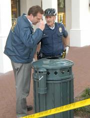 Officer Bob Casey (right) shows crime scene investigator Mike Ullemeyer the knife in the trash can