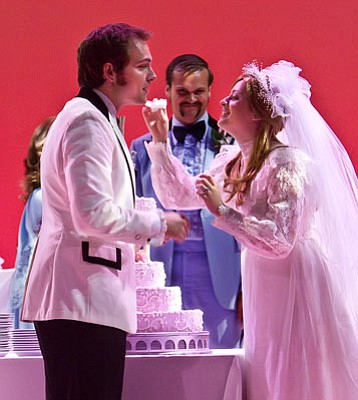 The groom, Dino Corelli (Alek Shrader), and the bride, Muffin Brenner (Olivia Savage), share their cake in front of the father of the bride, Snooks Brenner (Edward Parks), in the Music Academy's hit production of William Bolcom's wild and hilarious <em>A Wedding</em>.