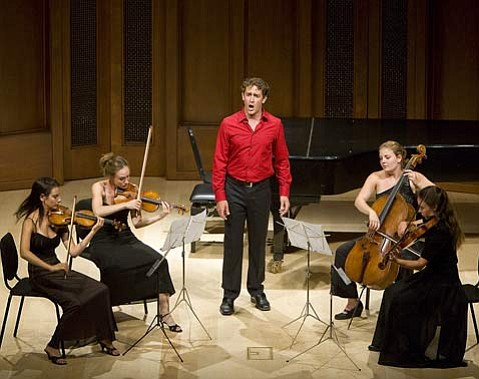 """Baritone Christopher Herbert (center) sang Samuel Barber's setting of Matthew Arnold's """"Dover Beach"""" accompanied by a string quartet. Seated, left to right: Michelle Abraham, Dawn Gingrich, Jillian Bloom, and Tasha Clearman."""