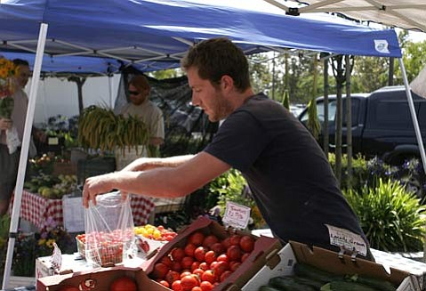Eli O'Donohue sells vegetables from Lane Farms at the Farmers Market in Goleta.