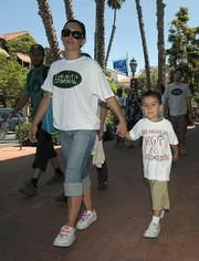 """My mom is not a criminal"" states the shirt of 4 year-old Angel Quinone (right) walking with mom Alisha Dally"