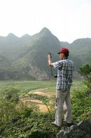 Graduate student Wu Zhi records the location of a Cycas debaoensis using a Global Positioning System (GPS) in Fuping Valley.