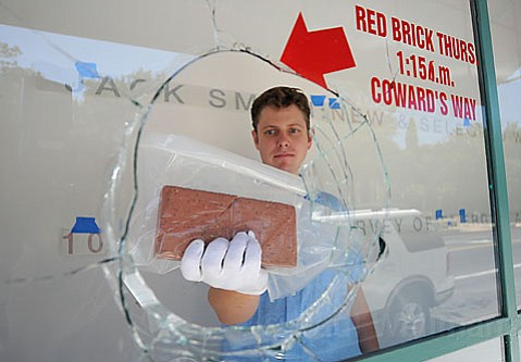 Jeremy Tessmer holds the brick that was thrown through the Sullivan Goss Gallery's display window, which is adorned with the gallery owner's comments on the act.