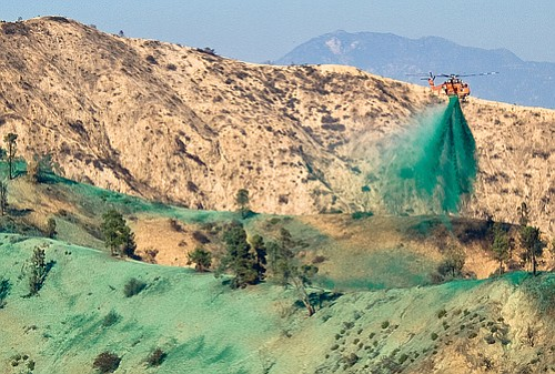 Helicopter sprays hydromulch on the hillsides to minimize erosion during the winter rains.