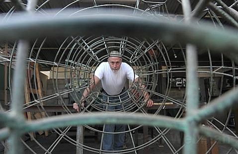 """Wild wires: Artist Ed Inks stands within the wire frame of his piece, """"The Birth of Bacchus,"""" which was removed from State Street entirely after it was damaged twice, presumably by passers-by."""