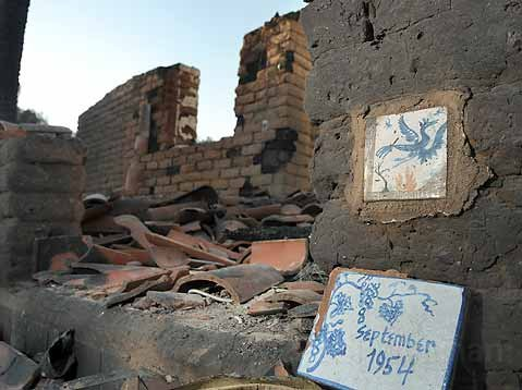 Tiles become symbols of the destruction of the Neely home on Mountain Drive. One commemorates the date of its construction; the other is a phoenix rising from flames.