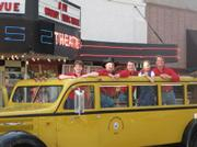 Dan Miller's Cowboy Music Revue poses in historic Yellowstone bus in downtown Cody.
