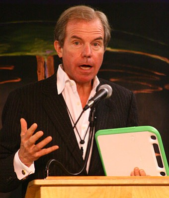 Linking up:  Nicholas Negroponte, founder of One Laptop Per Child, speaks at Kellogg Elementary School last Friday with his innovation, the XO laptop, in hand, demonstrating its durability.