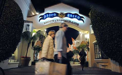 CITY SIDEWALKS, BUSY SIDEWALKS:  Shoppers skitter around State Street's Paseo Nuevo on Monday evening, many hoping to find deals. Shop owners are hoping, too-specifically that news of fiscal doom and gloom won't scare customers into keeping their pocketbooks closed.