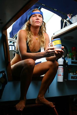 Clark gears up for another day at sea aboard <em>Swell</em> with her ritual cup of coffee.