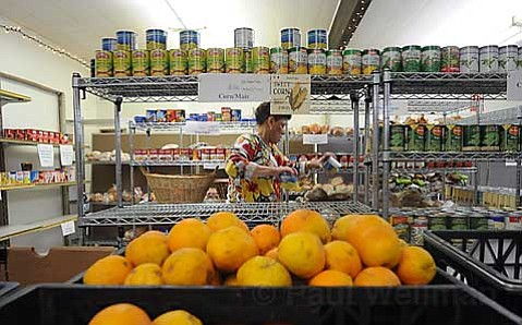FOOD FRENZY:  Lisa Gosdschan, staffer at the Catholic Charities food pantry on Haley Street, stocks shelves to offset an increased use of the service. The ailing economy has meant similar challenges for such facilities throughout the county.