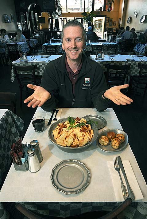 Palazzio owner Ken Boxer presents one of the unique State Street restaurant's massive servings, Papa Ruby's Rigatoni, with plenty of garlicky rolls on the side.