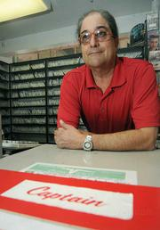 Joe Lombardo, owner of Captain Video for the past 17 years, behind the counter