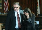 Hilary Dozer (left) comforts Kathy Tacadena, wife of slain Frank Tacadena after her statements to the court