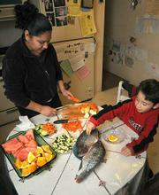 Guadalupe prepares a dinner of fish soup laden with fresh vegetables as Geraldo Jr. sneaks a taste.