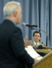 Dan Singer listens to Amerikaner (left) address the Goleta City Council.