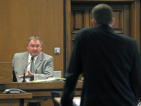 Holland on the stand, answering questions from Pappas's attorney.