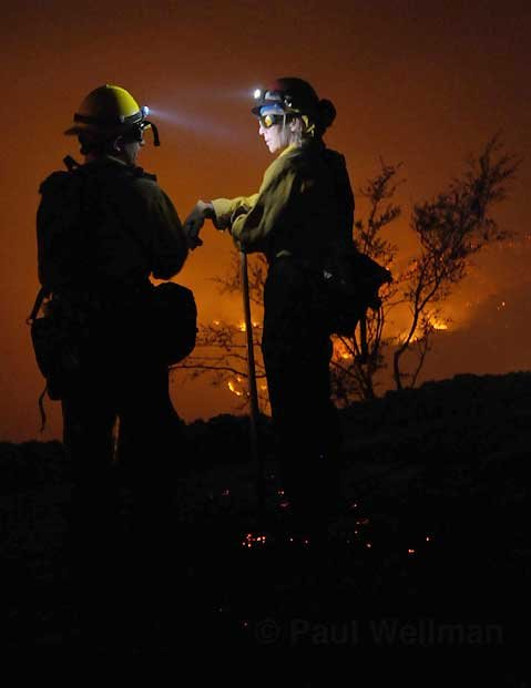 Santa Barbara County Fire Captain Nikki Stevens (right) talks with firefighter Bryon Fernandez (left) about plans for protecting the last house on Spyglass Ridge Road, as the Jesusita Fire burns in the background.